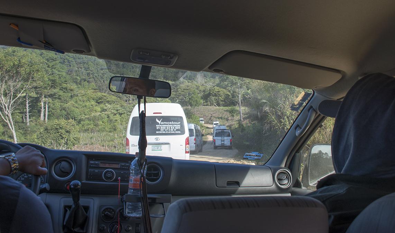 Convoy of tour vans on mountain road detour.