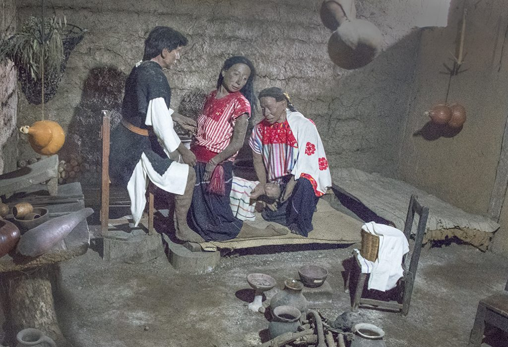 Diorama depicting midwife assisting a Mayan couple with childbirth.